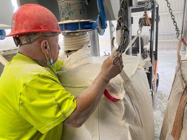 Supreme Perlite employee filling a product bag of perlite
